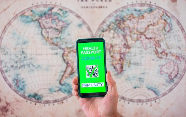 ワクチン接種のグリーンカードパスポート健康証明書と携帯電話を持っている人間の男性の手