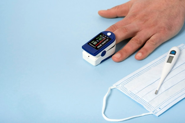 Human male hands pulse oximeter used to measure pulse rate and oxygen levels with medical blue background with copy space.