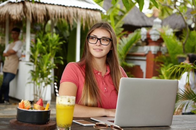 Human, modern technology and communication concept. attractive businesswoman in stylish glasses sitting in front of open laptop at wooden table with cocktail, fruit bowl
