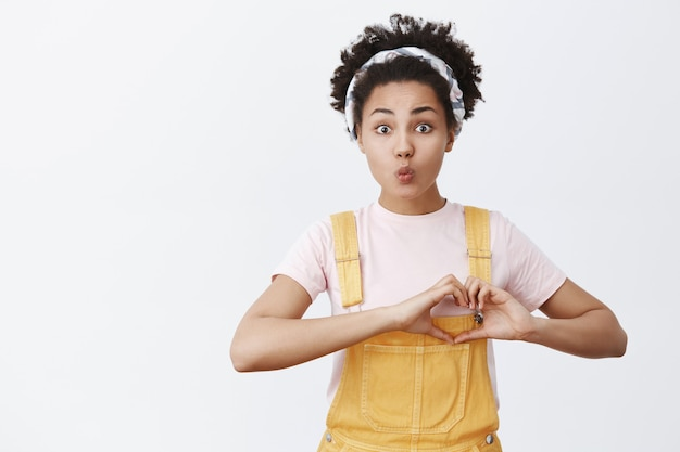 Human needs love. portrait of hopeful cute and tender african american in yellow overalls and headband, showing heart gesture near chest and folding lips in kiss, posing over gray wall