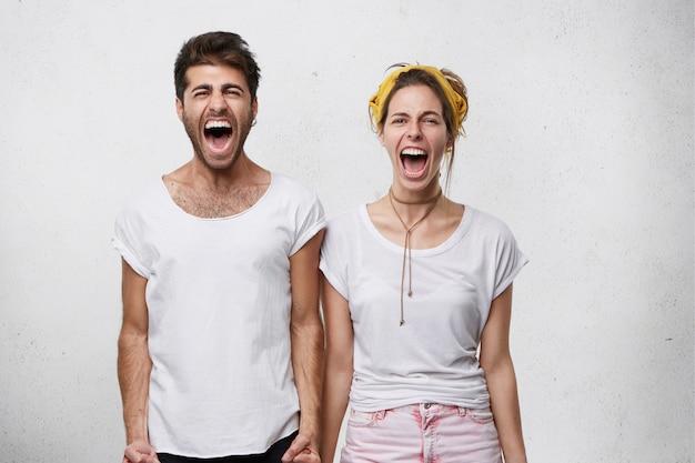 인간의 부정적인 감정, 반응, 감정 및 태도. 비명을 지르는 절망적 인 젊은 백인 부부의 허리 업 초상화, 서로 가까이 서있는 동안 실내에서 다투는 동안 소리