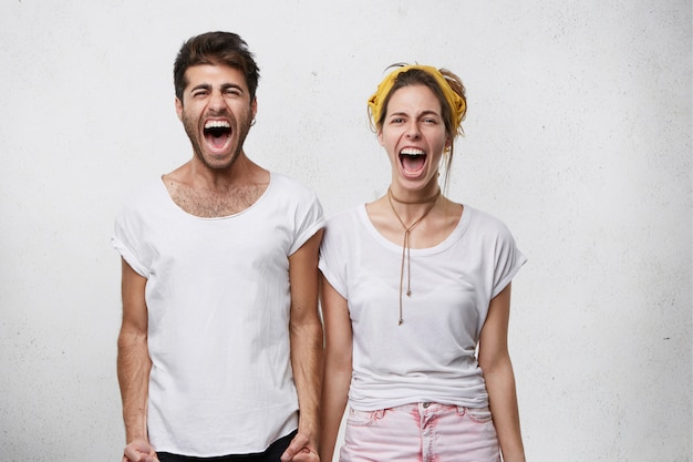 Human negative emotions, reaction, feelings and attitude. waist-up portrait of stressed desperate young caucasian couple screaming, shouting while quarrelling indoors, standing close to each other