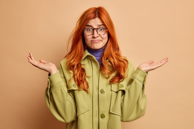 Human perception concept. doubtful confused hesitant ginger woman raises palms and shrugs shoulders questioned faces difficult choice wears fashionable coat.