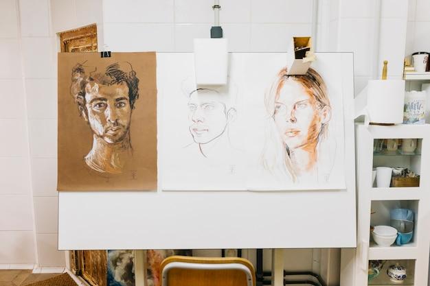Human portraits hanging on easel