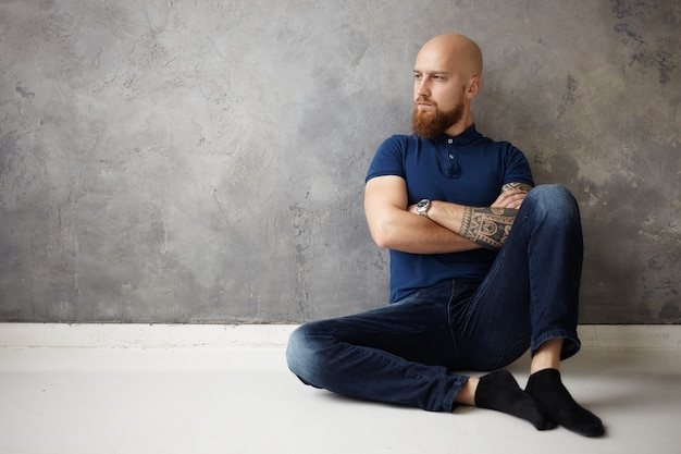 Human reaction, attitude and life perception. displeased angry young bald guy with stubble sitting on floor in empty room, being offended by his girlfriend during fight, crossing arms and pursing lips