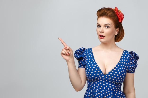 人間の反応、感情、感情。完全な不信と驚きで口を開けるヴィンテージのドレスを着た魅惑的な感情的な若いヨーロッパの女性、壁に衝撃的な内容を示し、人差し指