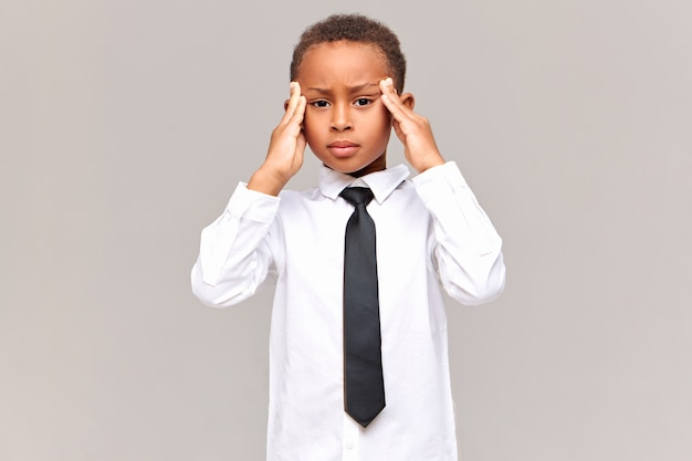 Human reaction, feelings and attitude.  frustrated unhappy african pupil in school uniform massaging temples, suffering from headache, being stressed with lot of home assignment