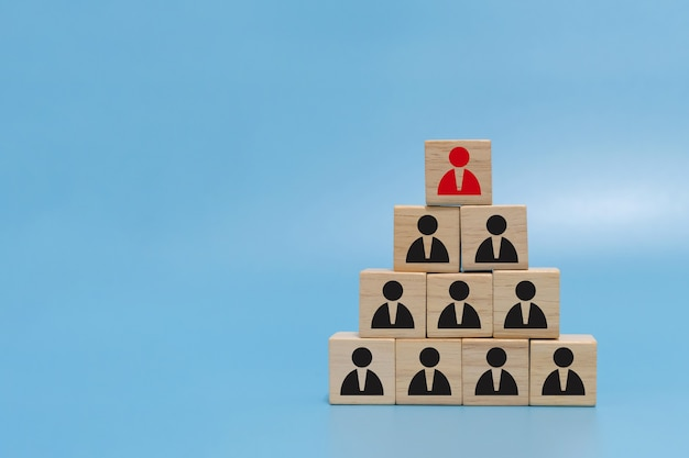Human resource. boss icon on wooden cube block on top pyramid stack on blue background with copy space, creative, business management, team leader, business strategy, human resource management concept