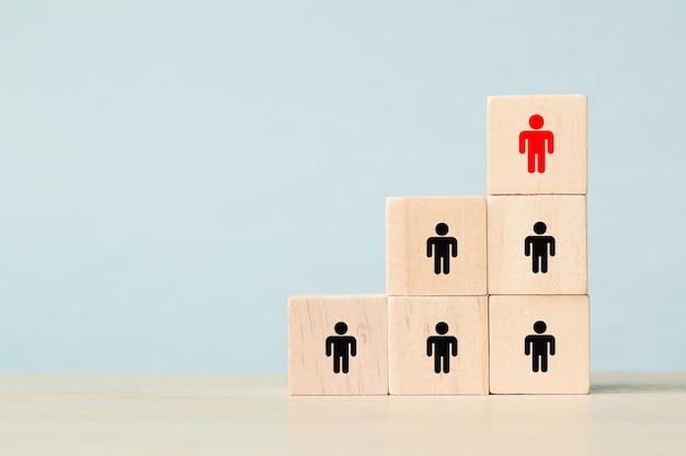 人的資源管理と採用ビジネスチームの概念。上部のピラミッドに木製の立方体ブロックを置く手