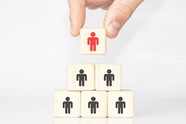 Управление человеческими ресурсами и концепция бизнес-команды набора. рука кладет деревянный кубик на вершину пирамиды