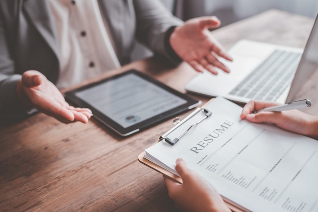 人事マネージャーは、求職者に仕事の説明をしてから、応募フォームに履歴書を記入して、会社での採用を検討しています。