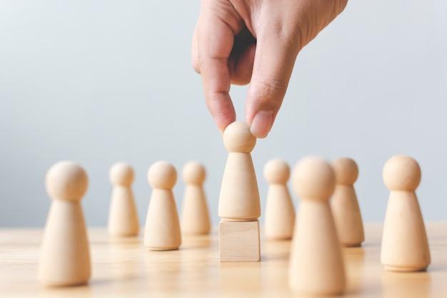 Управление персоналом, управление талантами, подбор персонала, успешная бизнес-команда лидер концепции. рука выбирает деревянного человека, выделяющегося из толпы.