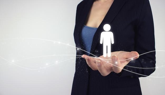 Human resources hr recruitment employment concept. hand hold digital hologram human on grey background. recruitment employment headhunting concept.