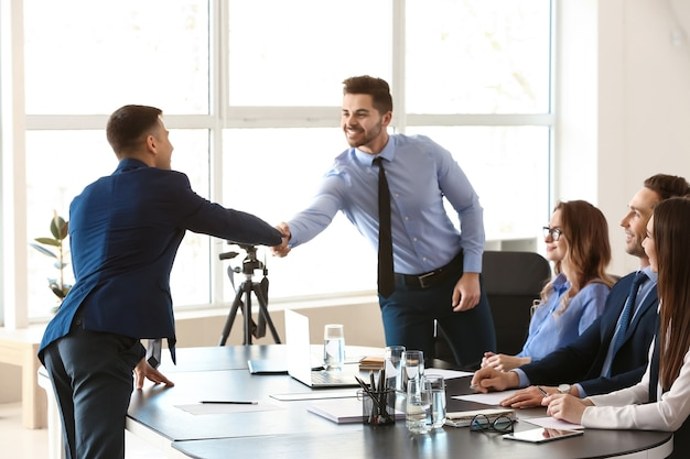 Human resources manager shaking hands with applicant after successful interview