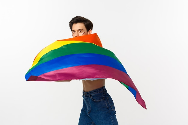 Human rights and lgbtq community concept. young queer person with glitter on face, waving lgbtq flag with pride, standing over white background.