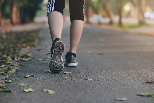 Human running on the park with close up shoes