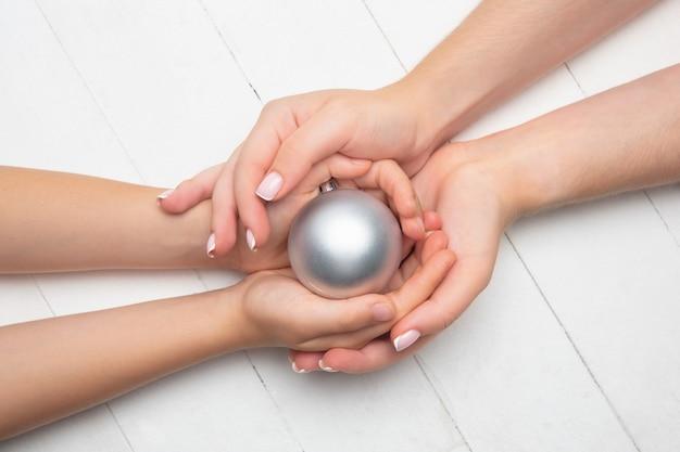 木製の白い背景で隔離のクリスマスボールを持っている人間の手。お祝い、休日、家族、家の快適さ、冬の休日、大晦日の概念。幸せな時間への贈り物。