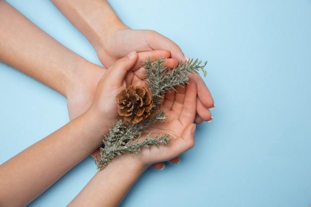 青い背景で隔離のクリスマスの装飾を持っている人間の手。お祝い、休日、家族、家の快適さ、冬の休日、大晦日の概念。幸せな時間への贈り物。