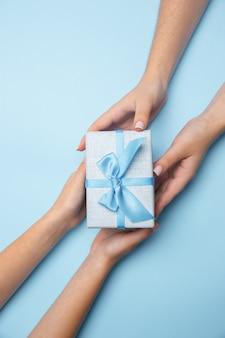 青い背景で隔離のプレゼント、ギフト、サプライズボックスを持っている人間の手。お祝い、休日、家族、家の快適さ、冬の休日、大晦日、誕生日、記念日の概念