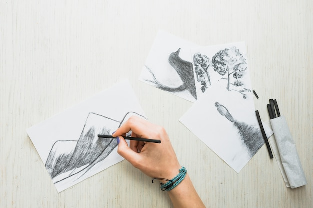 Human's hand sketching on paper with charcoal stick near beautiful hand drawn drawing