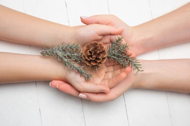白い背景で隔離の装飾を保持している人間の手。お祝い、休日、家族、家の快適さ、冬の休日、大晦日の概念。幸せな時間への贈り物。