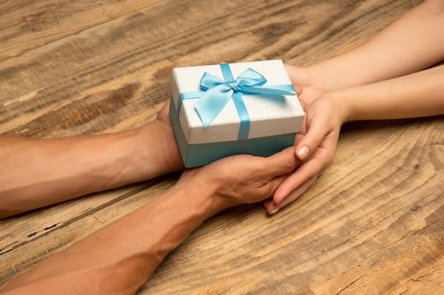 木製の背景に分離された装飾を保持している人間の手。お祝い、休日、家族、家の快適さの概念。幸せな時間への贈り物。