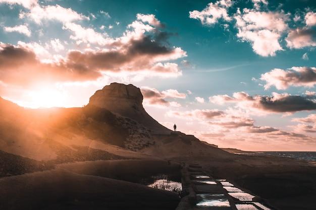 흐린 푸른 하늘 아래 일몰 동안 바위 산에 서있는 인간의 실루엣