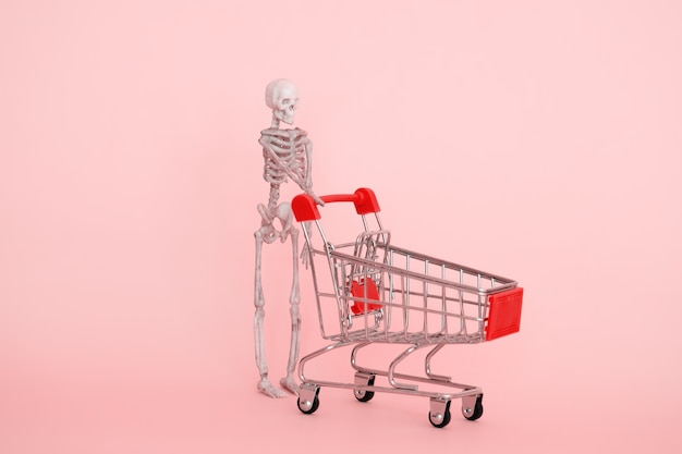 Human skeleton with shopping trolley on a pink background selective focus