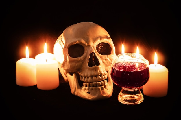 인간의 두개골과 어두운 정물 제단에 있는 불타는 초 사이에 어두운 발포성 액체 유리