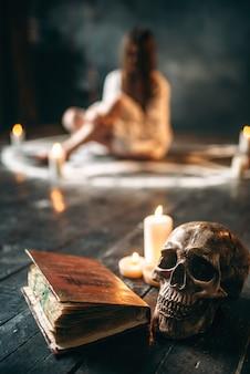 Человеческий череп и старая книга заклинаний на черном деревянном полу, женщина в белой рубашке сидит в круге пентаграммы со свечами