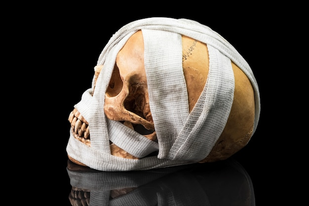 Human skull bind with dirty bandage on dark background