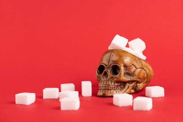 赤い背景に洗練された白い砂糖の立方体で満たされた人間の頭蓋骨。セレクティブフォーカス。スペースをコピーします。 Premium写真