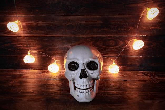 Human skull and luminous garland with halloween pumpkin lamps on dark wooden background