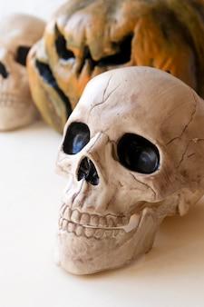 Human skull near jack-o-lantern