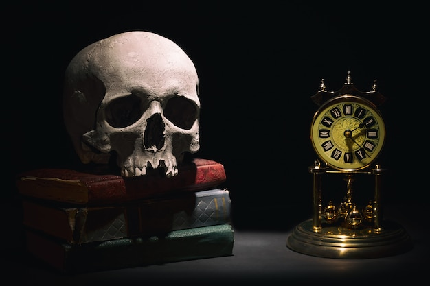 Human skull on old books near retro vintage clock on black background under beam of light.