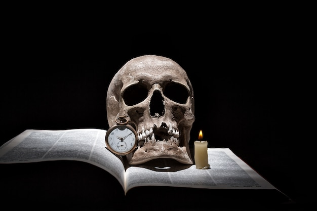 Human skull on old open book with burning candle and vintage clock on black background under beam of light