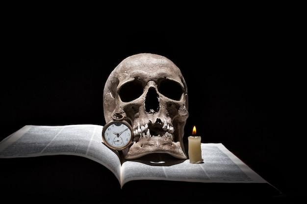 Человеческий череп на старой открытой книге с горящей свечой и старинные часы на черном фоне под лучом света