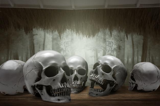 幽霊の森と木製のテーブルの上の人間の頭蓋骨