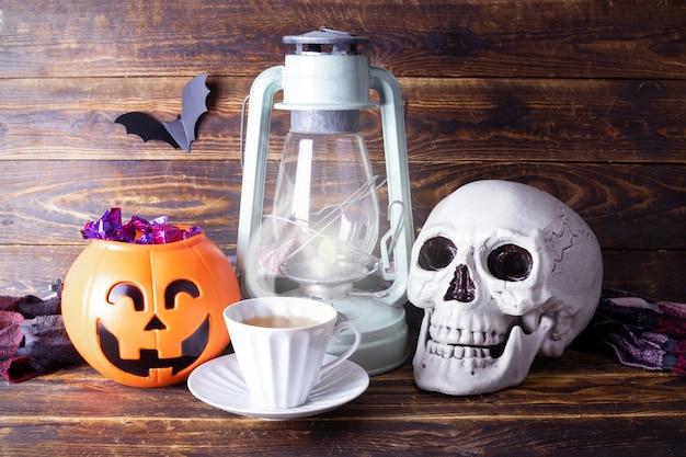 Корзина из тыквы с черепом и конфетами, керосиновая лампа и чашка чая на деревянном фоне, бумажная летучая мышь