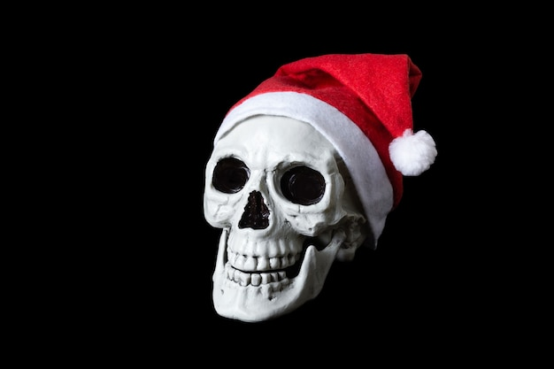 Human skull in red cap of santa claus. isolated on black surface.