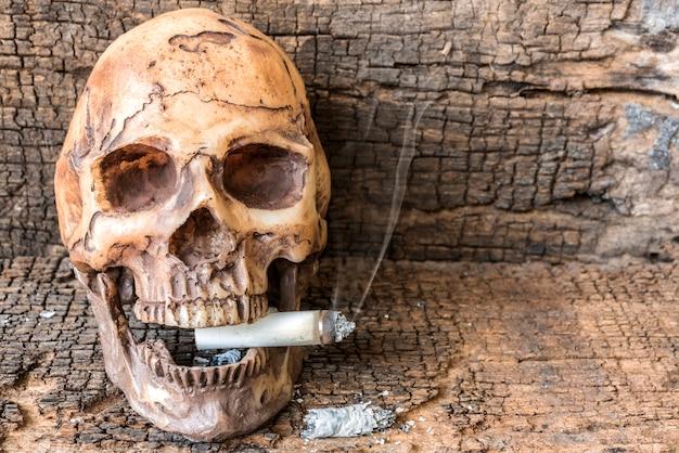 Human skull smoking cigarette with smoke