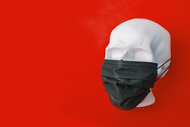 Human skull wearing a protective mouth mask. isolated on red background