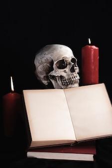 本のモックアップとキャンドルで人間の頭蓋骨