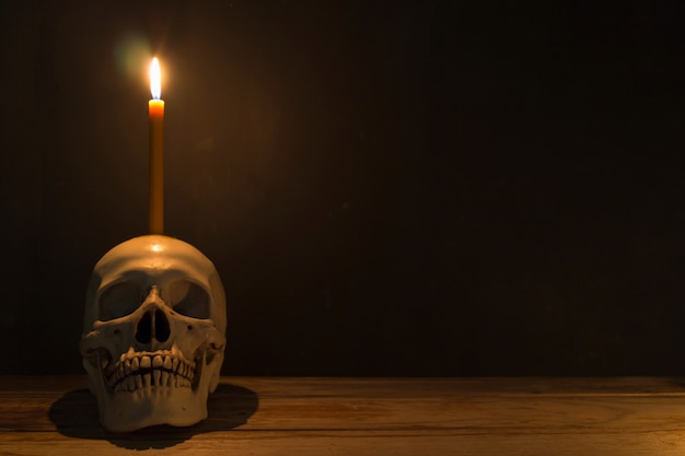 Human skull with candle light on wooden table in the dark background