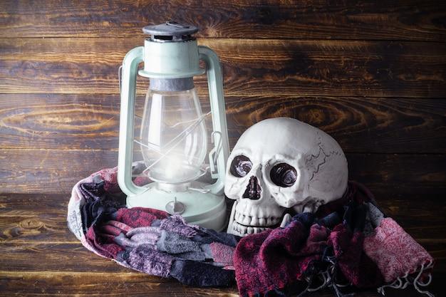 Человеческий череп с красочным шарфом и светящейся керосиновой лампой на фоне деревянной доски