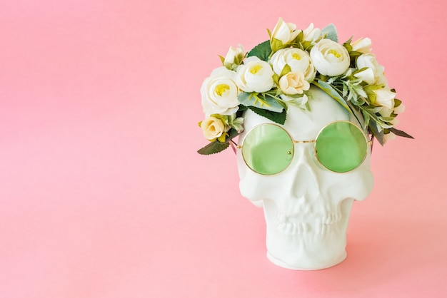 Human skull with green glasses and flowers isolated