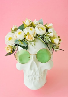 Human skull with green glasses and flowers on white background