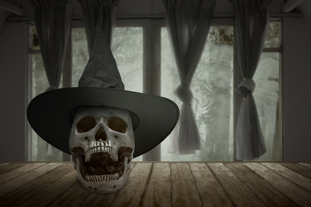 Human skull with a hat on a wooden table in an abandoned house