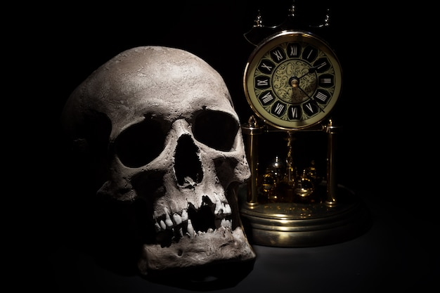 Human skull with vintage clock close up on black