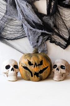 Human skulls near spooky jack-o-lantern